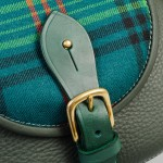 Leather fastening on tartan saddle bag