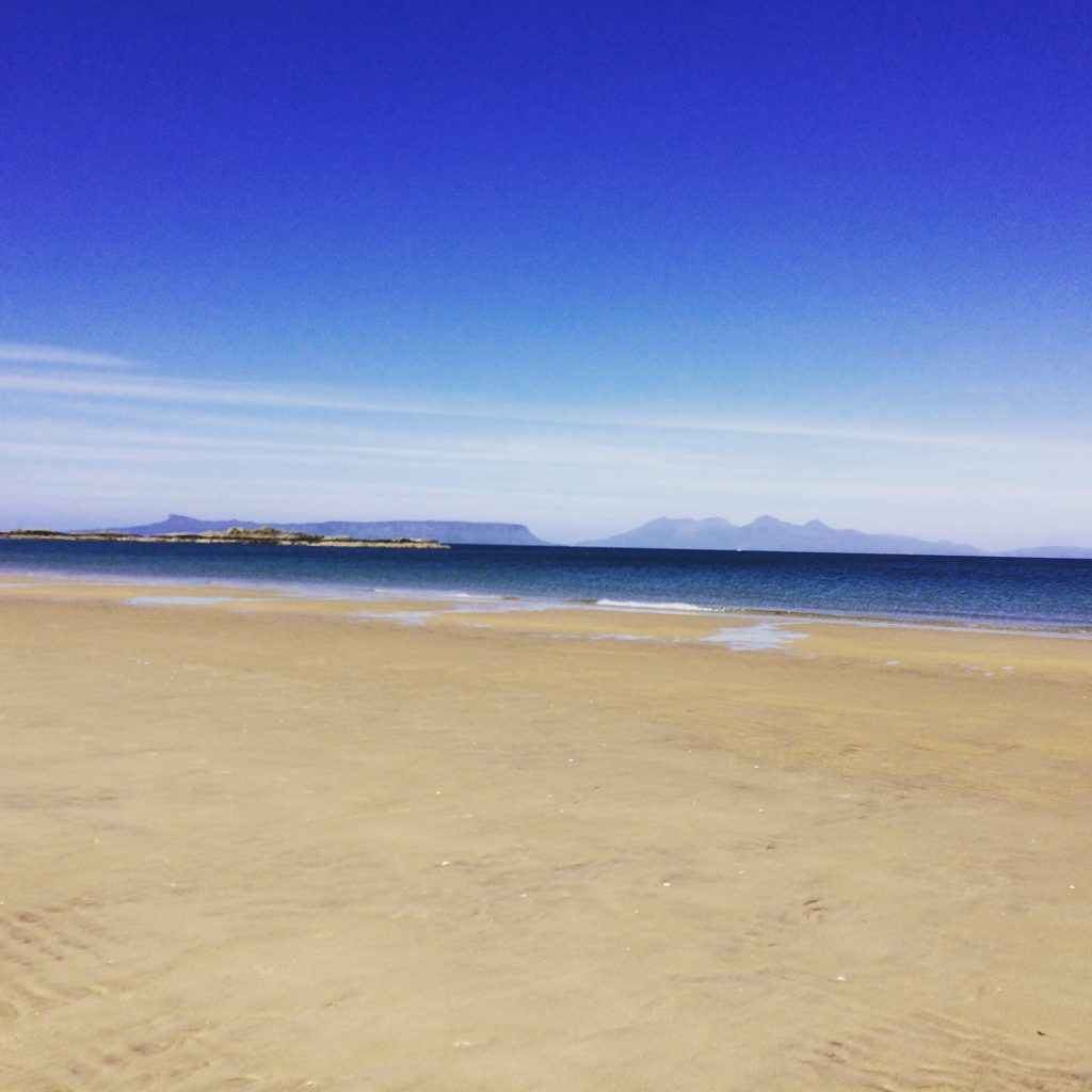 Camusdarach beach, golden sand and blue sky with islands in the distance